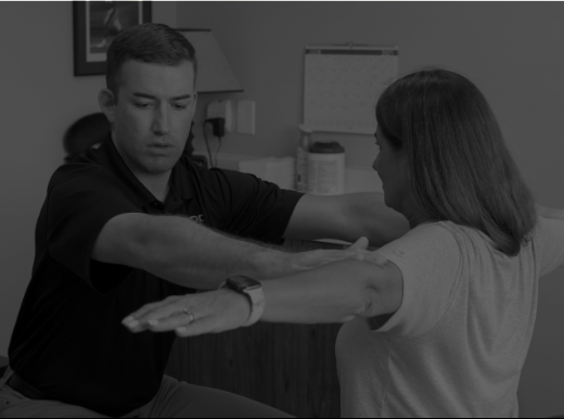 Physical therapist working with a patient with arms outstreched