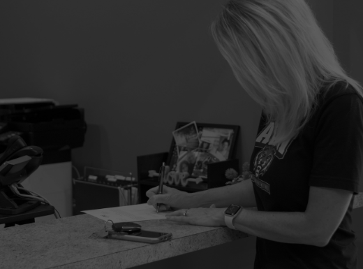 Person writing on piece of paper on a counter