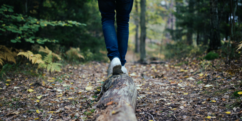 Close up image of person walking on a log in the woods