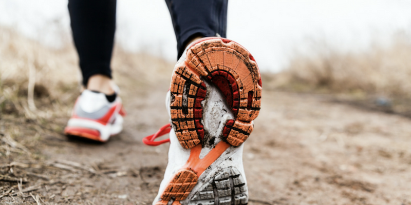 Close up image of running shoes on a muddy trail