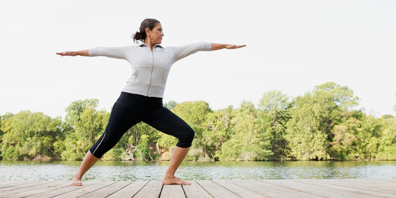 Person in athletic gear doing yoga on a dock