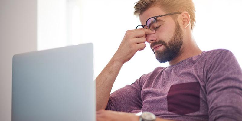 Person pinching bridge of nose looking at computer screen