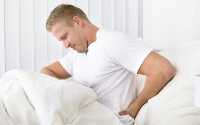 Person holding their lower back with a pained expression while sitting in bed