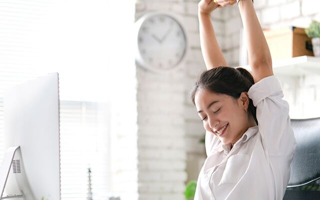 Person sitting at a desk and stretching their arms above their head